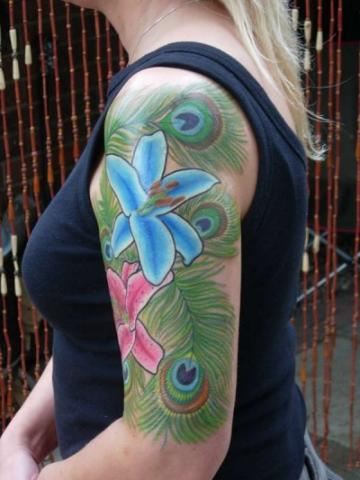 Цветная тату на плече девушки - перья и лилии