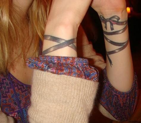 Цветная татуировка на запястьях девушки - браслет в виде ленты с бантом