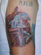 Цветная тату на плече в виде дельфина в кресле