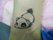 Цветная тату на запястье девушки - маленькая панда