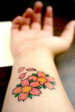 Цветная тату на запястье девушки в виде цветков сакуры