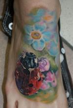Тату на ноге в виде божьей коровки с цветами