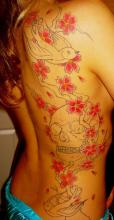 Тату на спине девушки в виде сакуры, черепа и ласточек